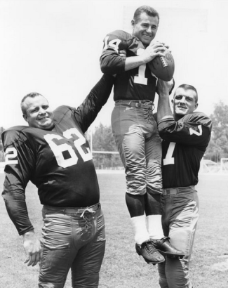 Two Redskins lineman hoist Eddie LeBaron.