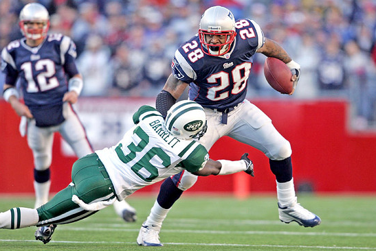 Corey Dillon tries to sidestep the Jets' David Barrett.