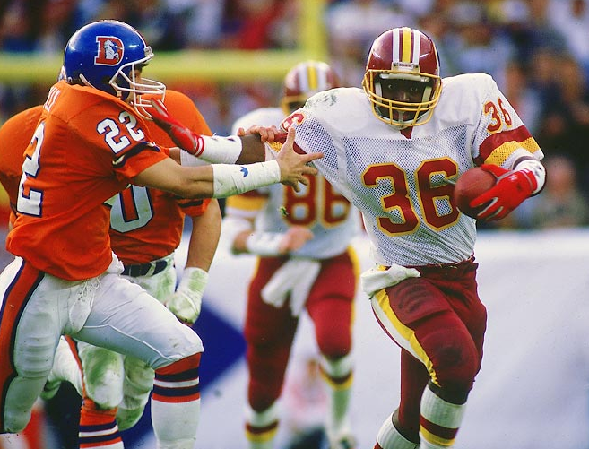 The Redskins' Timmy Smith keeps the Broncos' Tony LIlly at arm's length in Super Bowl 22.